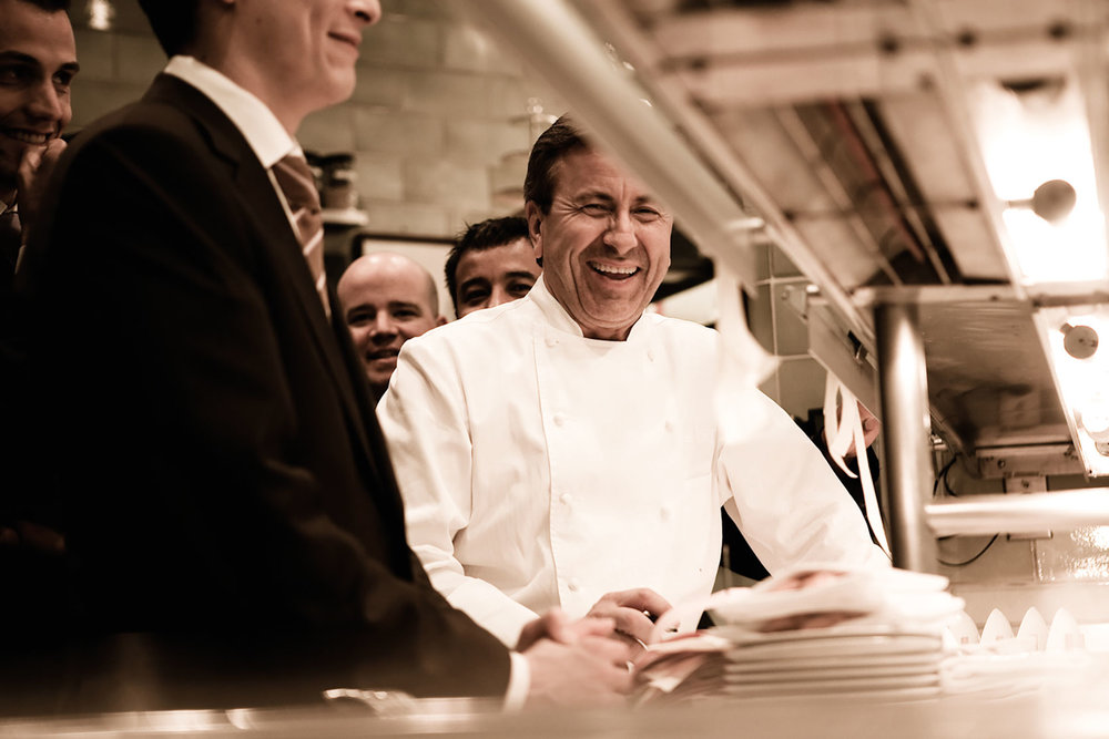"And yet he does. At 61 years old, Boulud — or DB, as people tend to refer to him, though to his face they mostly call him ""Chef"" — lords over a small empire of restaurants that are unabashedly French and, for the most part, unapologetically high-end. Six are in New York City, ranging from his Upper East Side flagship, Restaurant Daniel, where the seven-course, $234 tasting menu might include turbot en matelote and High Plains buffalo rossini, to the sausage-centric downtown DBGB Kitchen & Bar. Another nine stretch from Boston to Palm Beach, Toronto to London to Singapore; he visits them regularly. Moreover, those restaurants are all, somehow, cool. Or maybe ""au courant"" is the better way to describe them — the kinds of with-it places food lovers at all points on the economic and cultural spectrum actually want to visit, and tend to enjoy. Despite the sweep of history, they feel relevant. Not bad for a farm boy from Lyon. On a Monday afternoon in January, however, such grand themes felt distant. DB, compact in his chef's whites, his neatly brushed hair making the shift from deep brown to steely, was sitting in the Skybox, the low-ceilinged mini-suite (think Being John Malkovich's 7 1/2th floor) that overlooks the vast kitchen of Restaurant Daniel, and attending to one of the first of the day's many, many tasks: tasting a new beer-battered calamari with kaffir-lime cream, destined to appear on the menu at DBGB. ""This has to be more spicy and less salty,"" he said, a touch of his French accent remaining after 34 years in the United States. ""I mean, it's not salty but it's kind of…"" he trailed off. ""Anyway, that's an adjustment!"""